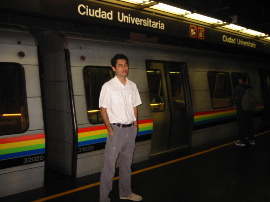 a man stands outside the Caracas subway at Ciudad Universitaria station
