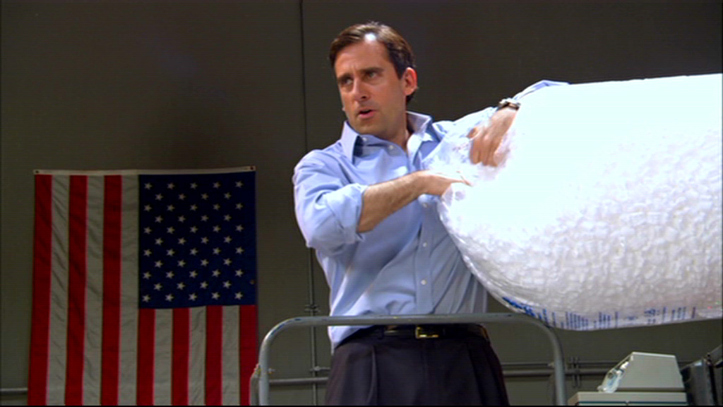Michael Scott opening a bag of popcorn peanuts in a warehouse in front of an American flag