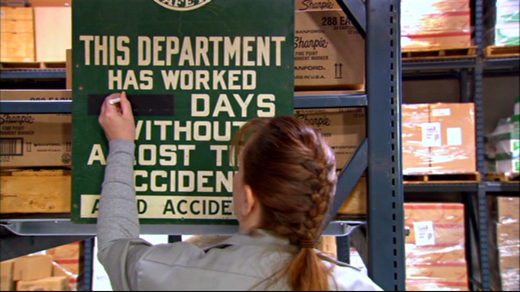 a warehouse worker from the Office fixing the employee injury sign